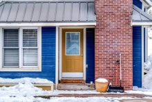 front of blue house with yellow door during snowy winter