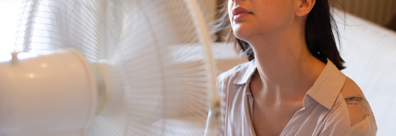 woman trying to stay cool in front of fan at home in summer