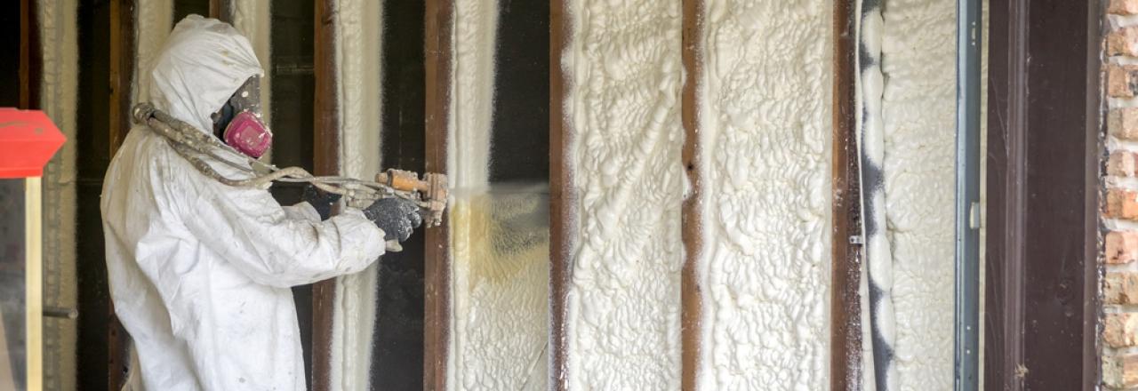 Technician adding spray foam insulation