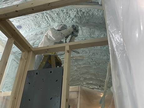 spray foam tiny house being installed on ceiling